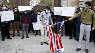 """Students wearing facemasks and holding signs saying """"Down with Israel"""" and others in Farsi burn Israeli and US flags in Tehran at a protest outside Iran's foreign ministry in Tehran (28 November 2020)"""