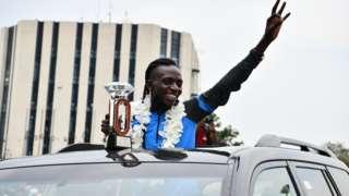 Athlete Francine Niyonsaba shows off her Diamond League trophy on her return to Burundi