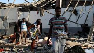 Migrants dey carry dia remaining belongings from di detention centre wey dey mainly African migrants afta di airstrike for di Tajoura suburb of di Libyan capital of Tripoli, Libya July 3