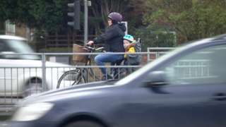 Woman riding bike with child in heavy traffic