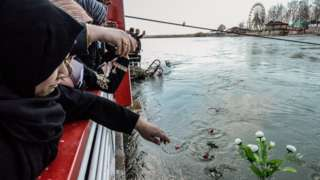 Iraqi women throw flowers into the River Tigris in Mosul in remembrance of those killed in a ferry accident (22 March 2019)