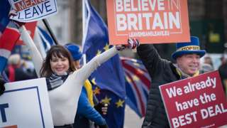 Pro and anti-Brexit campaigners wave placards outside Parliament