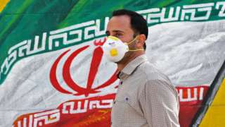 Iranian man wearing a mask in front of a mural of the national flag in Tehran (04/03/20)