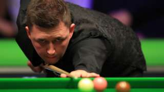 Kyren Wilson plays a shot in his match against Barry Hawkins