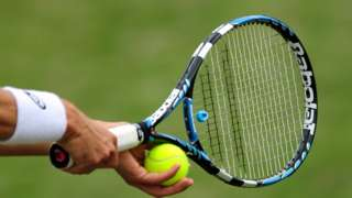 A generic shot of a tennis player about to serve a tennis ball with a tennis racket.