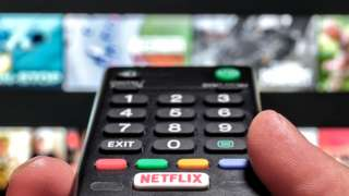 Stock image of TV remote control and the Netflix screen