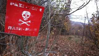 """A """"danger of death"""" sign is seen at a minefield in a woodland in Sarajevo, Bosnia and Herzegovina on November 20, 2017."""
