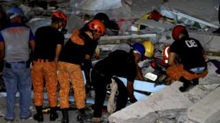 Emergency responders look through rubble of a commercial building following the earthquake
