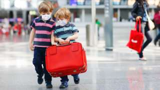 Two children with a suitcase in an airport