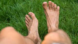 A man's bare legs as he sits on the grass