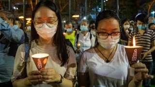 """香港维多利亚公园两名手持烛光的女示威者为北京""""六四""""事件死难者默哀(4/6/2020)"""