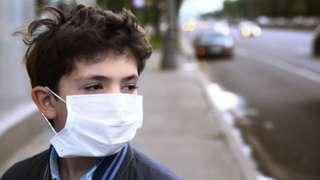 Boy wearing a face mask on a city street