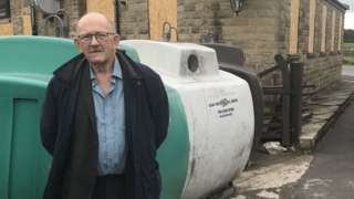 Conservative councillor Bill Armer standing in front of bottle banks