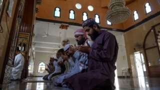 People praying at a mosque in Pakistan, defying government limits on the number of people gathering