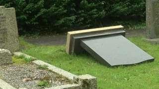 A gravestone lies face down