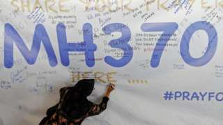 A woman writes on a message board after the disappearance of Malaysia Airlines flight MH370