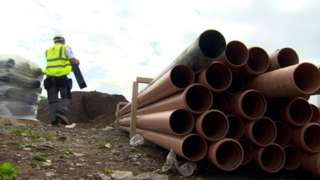 Pipes in the foreground while builder moves supplies