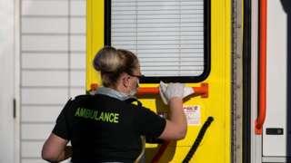 Ambulance worker cleans ambulance handrail