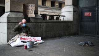 A homeless man wearing a protective face mask is seen in Westminster, as the spread of the coronavirus disease (COVID-19) continues, London, Britain