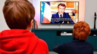 Pessoas assistem ao pronunciamento de Emmanuel Macron na TV