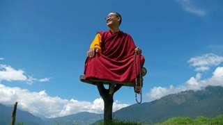 Rinpoche en un asiento elevado, detrás se aprecia el cielo