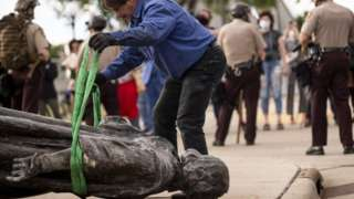 A statue of Christopher Columbus, which was toppled to the ground by protesters, in St Paul, Minnesota