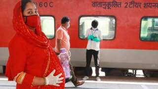 A pregnant women walk to board a Special AC train for New Delhi after the government eased a nationwide lockdown imposed as a preventive measure against the COVID-19 coronavirus, Howrah rail station in Kolkata on May 12, 2020.