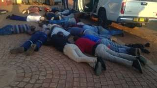 A picture of suspects being made to lie down after the attack