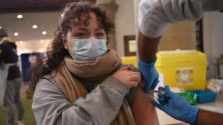 A woman receives the AstraZeneca Covid19 vaccine at an NHS vaccination centre in Ealing, west London, Britain 12 February, 2021. UK is close to completing first step of the vaccination programme, with 13.5m people having had a first jab according to NHS England.