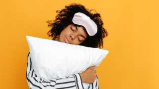 Woman hugging a white pillow, sleeping mask over her head, bright yellow background