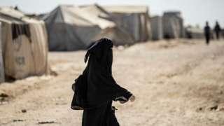 Suriye'nin kuzeydoğusundaki El Hashat'ta, IŞİD'in yabancı savaşçıların ailelerinin tutulduğu Kürt yönetimindeki El Hol kampında bir kadın yürüyor.