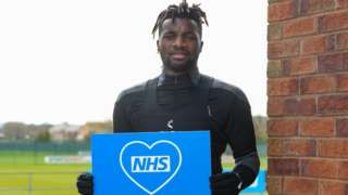 Allan Saint-Maximin Holds thank you NHS sign