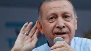 President Erdogan cups a hand to his ear in a listening gesture at a rally