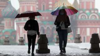 People walk under umbrellas in Red Square on 29 May 2020
