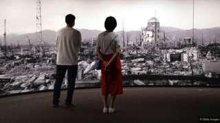 dvoje ljudi ispred slike rusevina