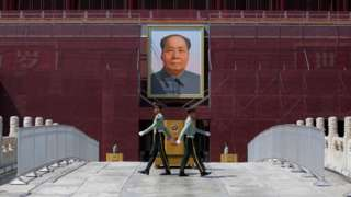 Paramilitary officers change guard in front of the portrait of the late Chinese chairman Mao Zedong in Tiananmen Square in Beijing, China May 7, 2019
