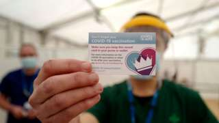medic holding up covid vaccination card