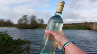 a swimmer brandishes a wine bottle full of water