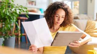 Stock image of a woman looking at a letter and a laptop