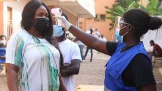 Un scrutateur vérifie la température corporelle des électeurs dans des mesures de coronavirus (Covid-19) alors qu'ils arrivent pour voter dans une université du Wisconsin lors des élections générales ghanéennes de 2020 à Accra, au Ghana, le 7 décembre 2020.