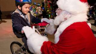 Boy on bike with Santa Claus