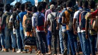 Workers carrying their belongings queue to board buses to go back to their homes in province during a government-imposed nationwide lockdown as a preventive measure against the COVID-19 coronavirus, at an industrial zone on the outskirts of Colombo on March 28, 2020