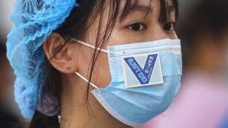 江苏省南京市浦口区一处核酸检测点内志愿者口罩上贴着鼓劲用的贴纸(中新社图片29/7/2021)