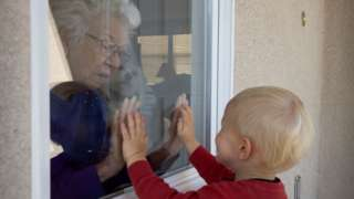 A baby visits an elderly neighbour though a glass window