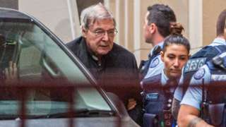 Police lead George Pell from a prison van into the court on Thursday