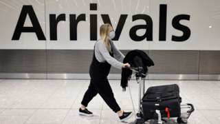 People arrive at Heathrow's Terminal 5 in west London on August 2, 2021 as quarantine restrictions ease.