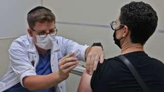 Homem sendo vacinado por profissional de saúde em Israel