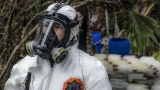 A Sinaloa state police officer works during the dismantle of one of the three clandestine laboratories producers of synthetic drug, mainly methamphetamine in El Dorado, Sinaloa state, Mexico on June 4, 2019.