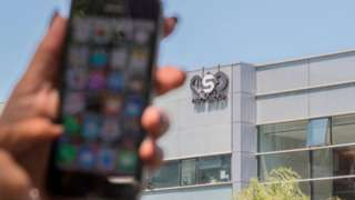 Woman uses iPhone in front of HQ of NSO group in Herzliya, Israel