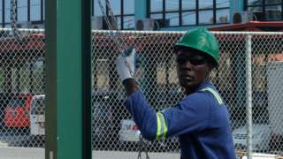 A man working in the oil industry in Guyana helps get equipment into place